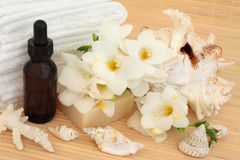 Purity. Spa and aromatherapy accessories with freesia flower blossom over bamboo background Stock Photos