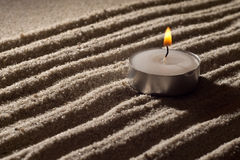 Purity Of Flame. Lit Tea Candle on White Sand in Abstract Lighting Royalty Free Stock Images