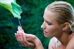 Purity and nature harmony. Beatiful young woman with open hands take fresh flowing water from a green leaf in the nature. Symbol of harmony and body care Stock Images