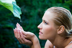 Purity and nature harmony. Beautiful young woman with open hands take fresh water drops from a green leaf in the nature. Symbol of harmony and body care stock photo