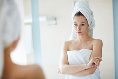 Purity. Young woman looking at herself in mirror after bath Royalty Free Stock Photos