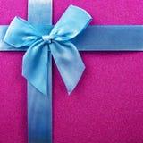 purpere achtergrond met blauw lint, blauwe boog, Kerstmisachtergrond, Kerstmisgiften Royalty-vrije Stock Afbeeldingen