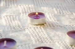 Purpere aromatische kaarsen op een sjaal stock afbeeldingen