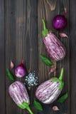 Purpere aubergine, knoflook en basilicumbladeren van hierboven op de oude houten raad met vrije tekstruimte Verse oogst van de tu Royalty-vrije Stock Afbeeldingen