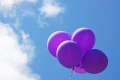 Purpere ballons die in blauwe hemel drijven Stock Afbeeldingen
