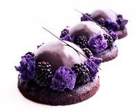 Purpere chocoladedesserts met glanzende spiegelglans en braambessen stock afbeeldingen