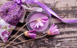 Purpere die oogschaduw, door bloemen en een pakket van lavendel op donkere geweven houten achtergrond wordt omringd De manier en  Royalty-vrije Stock Foto