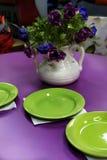 Purpere eettafel met groene platen Stock Foto