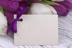 Purpere en witte tulpen met Witboek op een witte houten achtergrond met kaart voor tekst De dag van de vrouw 8 Maart De dag van d Stock Afbeelding