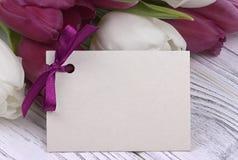 Purpere en witte tulpen met Witboek op een witte houten achtergrond met kaart voor tekst De dag van de vrouw 8 Maart De dag van d Royalty-vrije Stock Afbeeldingen