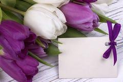 Purpere en witte tulpen met Witboek op een witte houten achtergrond met kaart voor tekst De dag van de vrouw 8 Maart De dag van d Stock Foto