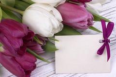 Purpere en witte tulpen met Witboek op een witte houten achtergrond met kaart voor tekst De dag van de vrouw 8 Maart De dag van d Royalty-vrije Stock Foto