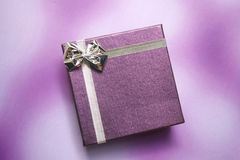 Purpere giftdoos op purpere achtergrond Stock Foto's