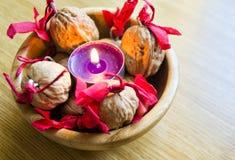 Purpere kaars met verfraaid wallnuts in een houten kom stock foto