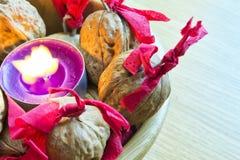 Purpere kaars met verfraaid wallnuts in een houten kom royalty-vrije stock afbeeldingen