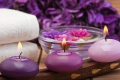 Purpere kaarsen en bloemen in kuuroord dat (1) plaatst Royalty-vrije Stock Afbeeldingen