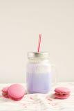 Purpere koffie in de gestileerde kop van de metselaarkruik met macarons en kleurrijke decoratie Bosbessenmilkshake, cocktaill, fr Royalty-vrije Stock Foto's