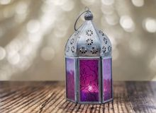 Purpere lantaarn op een houten oppervlakte Gouden bokehachtergrond met exemplaarruimte royalty-vrije stock foto's