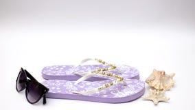 Purpere pantoffels en zonnebril en overzeese shell op witte achtergrond - houd motie tegen stock footage