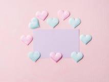 Purpere pastelkleurkaart en harten op roze geweven achtergrond Stock Afbeelding