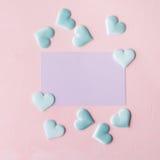 Purpere pastelkleurkaart en harten op roze geweven achtergrond Stock Afbeeldingen