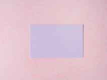 Purpere pastelkleurkaart op roze geweven achtergrond Stock Foto's