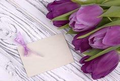 Purpere tulpen met Witboek op een witte houten achtergrond met kaart voor tekst De dag van de vrouw 8 Maart De dag van de moeder  Stock Afbeeldingen