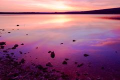 Purpere zonsondergang over overzees water Stock Afbeeldingen