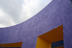 Purple. Curved purple and yellow building with sky in background Royalty Free Stock Image