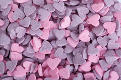 Purple ad pink candy hearts Royalty Free Stock Image