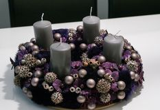 Purple advent wreath with baubles and four grey candles on a white table