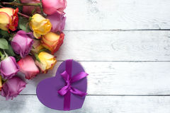 Purple And Yellow Roses, Box Present On White Wooden Background Stock Photos
