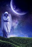 Purple Angel. A solemn looking angel in a field overlooking a galaxy setting Stock Images