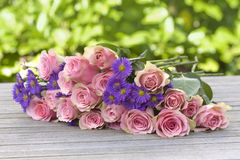 Purple aster and pink roses. Lying on a wooden table royalty free stock photos