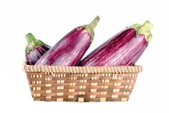 Purple aubergines in a straw basket Royalty Free Stock Photography