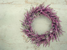 Purple autumn heather flower wreath. On green wooden vintage background with copy space Stock Image