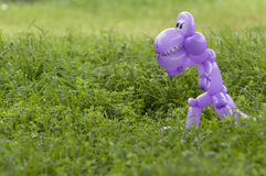 Purple balloon animal dinosaur in green grass of back yard Stock Image