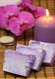 Purple Bars Of Soap. Candle burning, pebble, a orchid, a bottle with oil, soap, and more royalty free stock photo