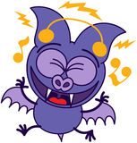 Purple bat listening to music Stock Images