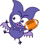Purple bat playing football. Purple bat in minimalistic style, with bulging eyes, sharp fangs and short wings while holding a foot ball and preparing to throw it Stock Photo