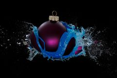 Blue liquid repleased by an exploding bauble Stock Images