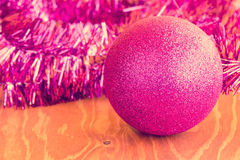 Purple bauble and tinsel on wooden background Stock Photos
