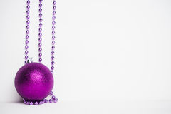 Purple bead on the white wooden background. Royalty Free Stock Image