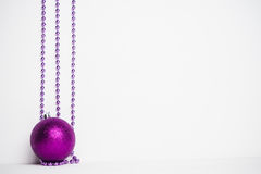 Purple bead on the white wooden background. Royalty Free Stock Images