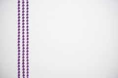 Purple bead on the white wooden background. Royalty Free Stock Photos