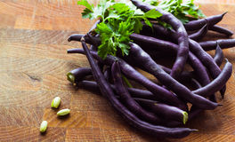 Purple bean pods. And leaves of parsley on a wooden cutting board royalty free stock image