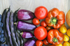 Purple Beans, grapes, tomatoes, peppers on light wooden surface. Autumn food background. Purple Beans, grapes, tomatoes, peppers on light wooden surface. Top Stock Photo