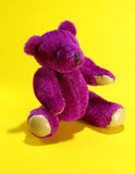 Purple Bear. A generic miniature plush toy bear sitting on a yellow backdrop Stock Images