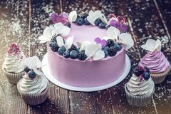 Purple beautiful cake decorated with berries, blackberries and blueberries on top with cupcakes on the festive table Royalty Free Stock Photo