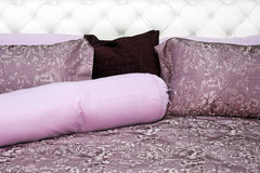 Purple bedding. Sheets with pillows on leather bed Stock Images